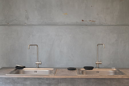 two gray sinks with faucets