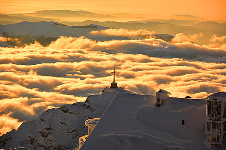 cross on top of snowy mountain surrounded by clouds