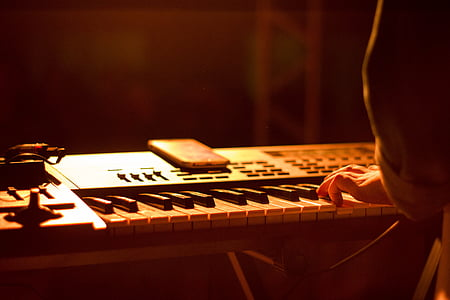 person holding electronic keyboard