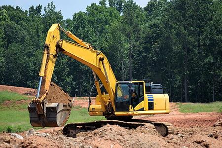 yellow excavator excavating on ground