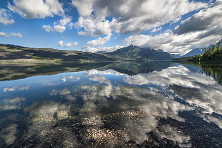 landscape photography of mountains surrounded by body of water during daytime