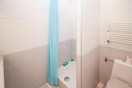 blue curtain hanging near white ceramic bathtub