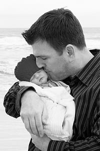 grayscale photo of man kissing baby wrapped in towel on seashore