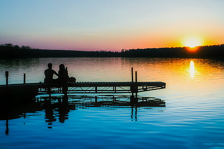 silhouette of two people sitting on docks near body of water