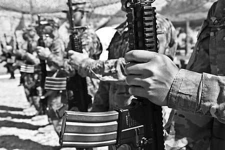 soldiers holding rifles in grayscale photography