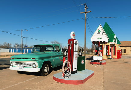 teal pickup truck parked at gasoline station