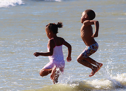 girl and boy playing on water during daytime