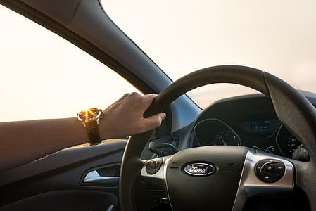 person holding gray Ford car steering wheel during daytime