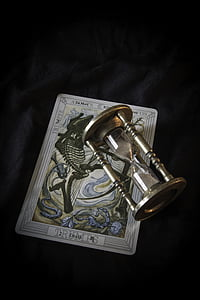 clear hourglass and white book