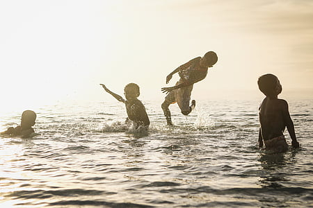 four boys swimming on sea during daytime