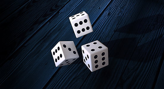 three dice on wooden tables