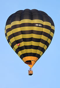 people riding on yellow and black hot air balloon