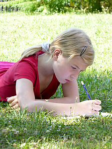 girl laying on grass field while writing on lined paper