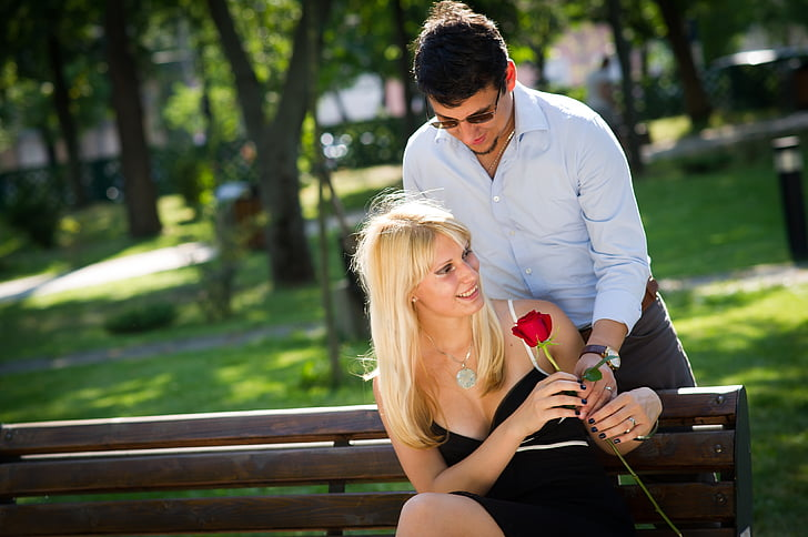 man giving a rose to woman