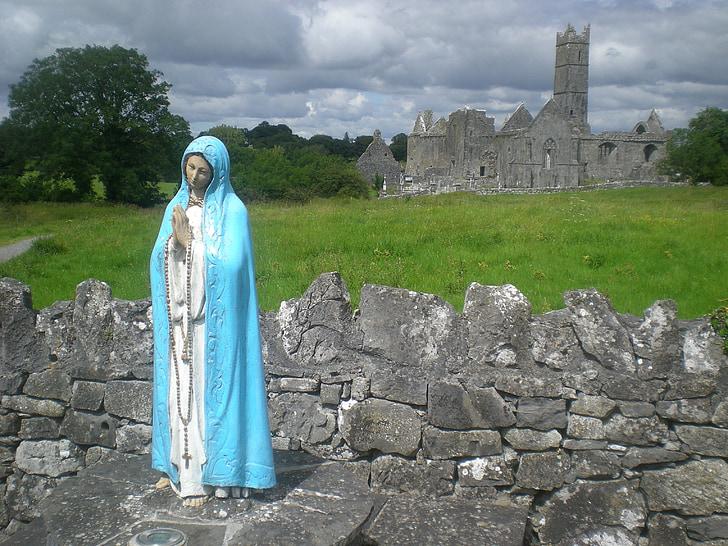 Virgin Mary statue near gray concrete building