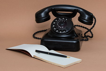 black rotary phone near notebook and pen