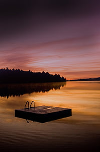 square wooden dock on body of water