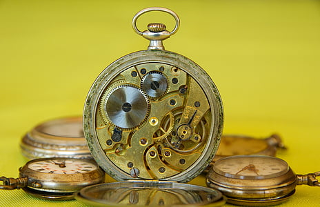 selective photography of round gold-colored and white pocket watch