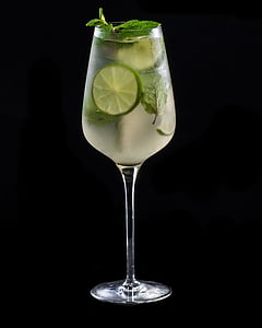 glass of beverage with lime on black surface