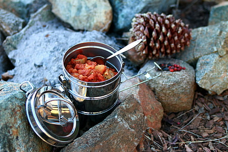 stainless steel tiffin box on rocks near brown pine cone during daytime
