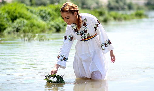 woman wears white and black floral dress stands on water near green grass