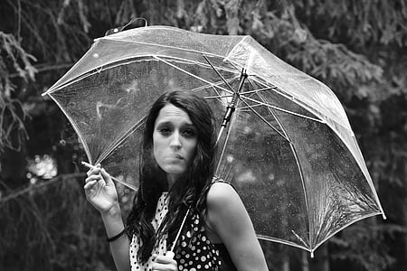 grayscale photo of woman holding umbrella and cigarette stick