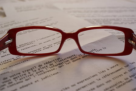 clear eyeglasses with red frames on top of book page