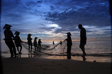 silhouette of people holding fish net on body of water