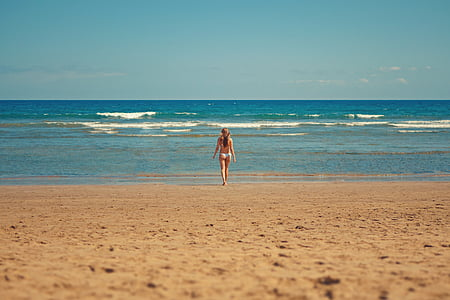 woman standing on seashore during daytime