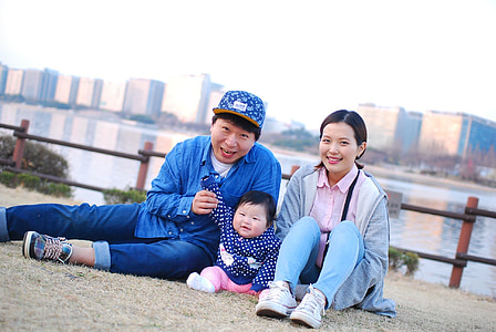 woman with man and child sitting on bank of river during daytime