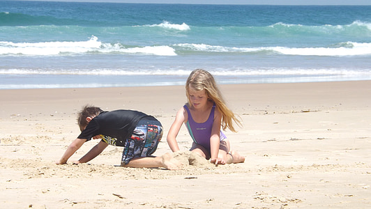 photography of boy and girl on beach