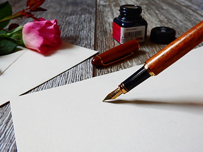 calligraphy pen pointing on white blank paper