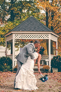 couple near gray wooden gazebo