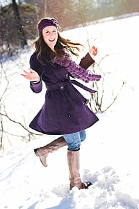 woman in purple coat on snow field