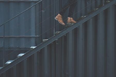 man wearing brown leather boots climbing on black metal stairs at daytime