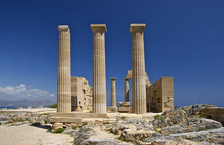 three columns with ruined structure