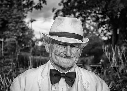 grayscale photo of man wearing formal suit and bucket hat