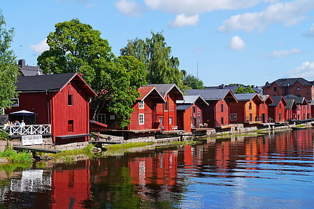 red and black wooden houses near water