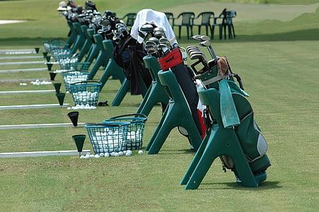 golf club in bags beside baskets on field