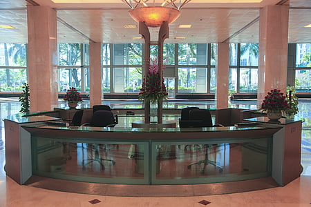 empty glass-top front desk in the lobby of a building