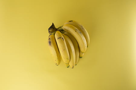 riped bananas on yellow surface
