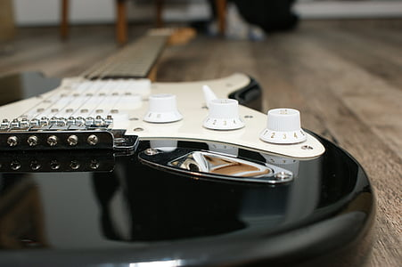 black and white electric guitar on floor