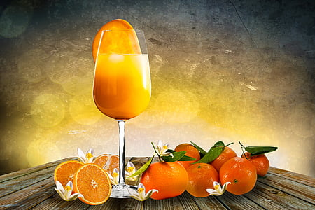 wine glass with orange juice on brown wooden table