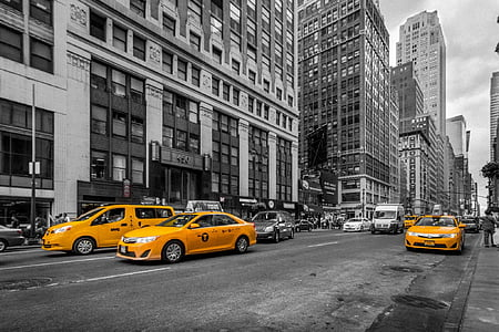 selective color photography of three orange taxis
