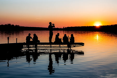 silhouette photography of six people on dock during sunset
