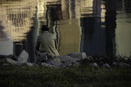 man sitting on grass facing body of water