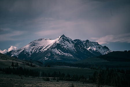 snow covered mountain during cloudy day