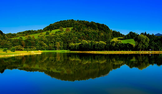 panoramic photography of hill with body of water