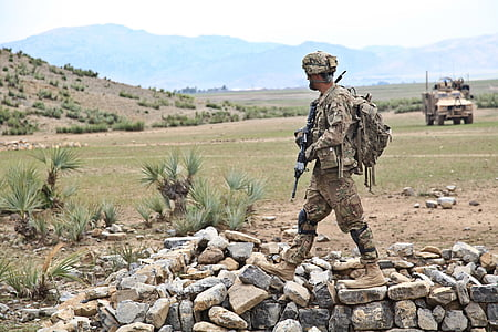 soldier holding assault rifle on gray and brown stones