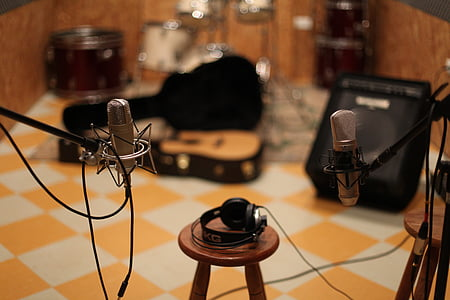 shallow focus photography of black headphones on brown wooden bar stool chair between microphones with stands